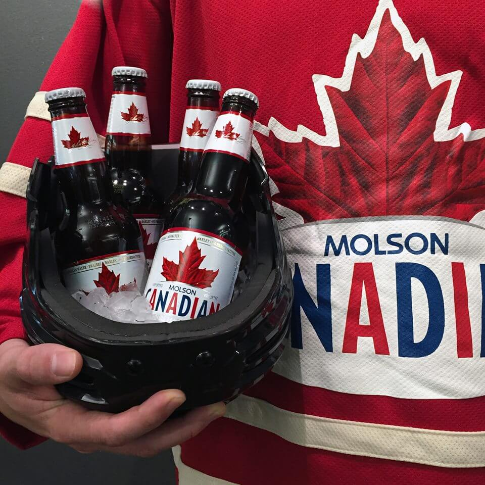 Person holding Molson Canadian Beer Bottles